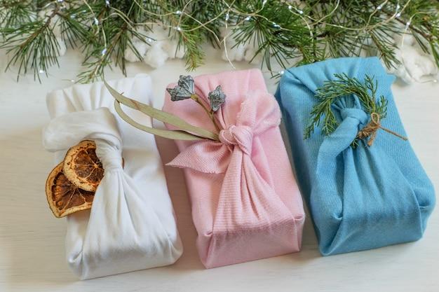 Cajas de regalo navideñas hechas a mano con cero residuos en tela reutilizable envueltas en el estilo tradicional japonés furoshiki.