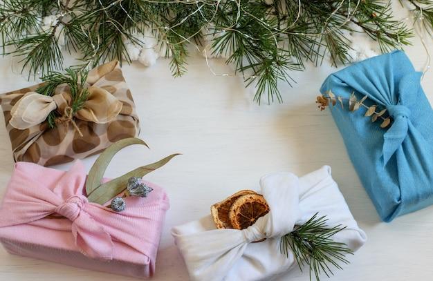Cajas de regalo navideñas hechas a mano envueltas en tela reutilizable al estilo japonés furoshiki.