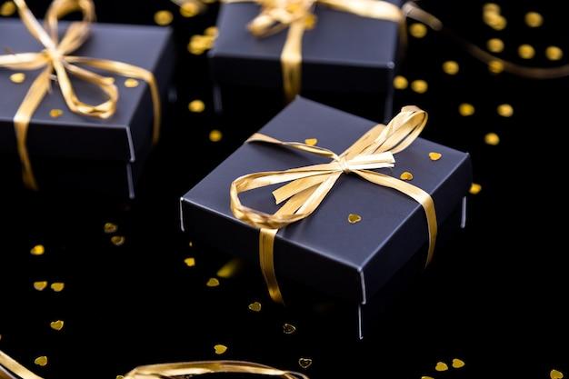 Cajas de regalo negras con cinta dorada sobre fondo de brillo