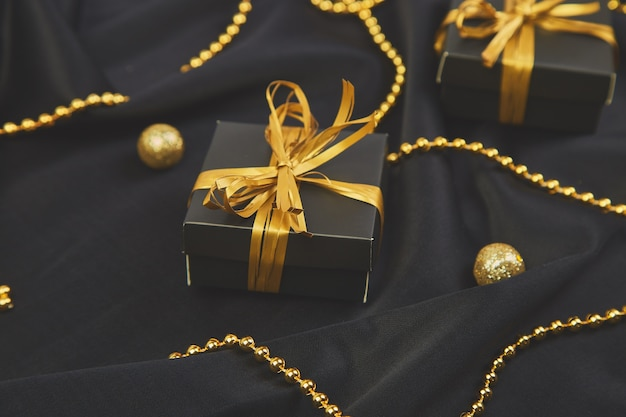 Cajas de regalo negras de lujo con cinta dorada.