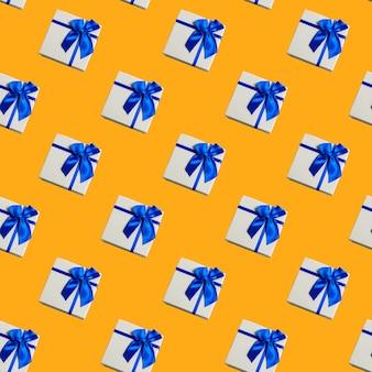 Cajas de regalo de patrones sin fisuras sobre amarillo concepto de vacaciones festivas.