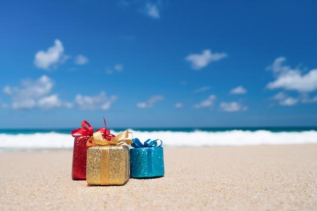 Cajas de regalo en la playa de arena. tours calientes o concepto de vacaciones de vacaciones con mar de verano.
