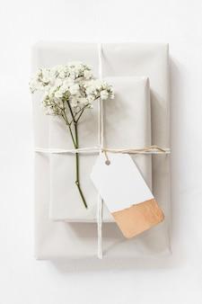 Cajas de regalo y ramitas de flores de aliento para bebés atadas con una cuerda y una etiqueta