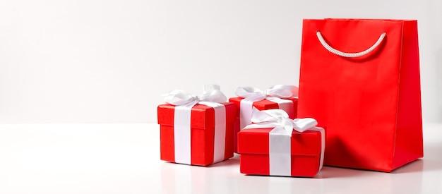 Cajas de regalo rojas y una bolsa sobre un fondo blanco.