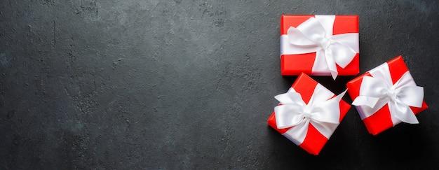 Cajas de regalo rojas con cintas blancas sobre fondo negro
