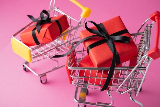 Cajas de regalo rojas con lazo negro en carrito de compras