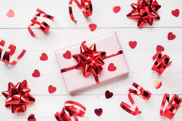 Cajas de regalo rosa con cintas rojas y lazos, corazones de confeti sobre un fondo blanco. copia espacio lay flat. tarjeta de felicitación para fiesta de cumpleaños, boda de san valentín.