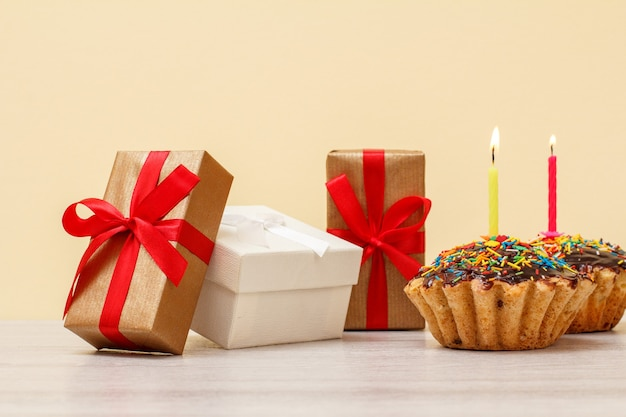 Cajas de regalo y sabrosos muffins de cumpleaños, decorados con velas festivas encendidas sobre fondo beige y madera. concepto de feliz cumpleaños.