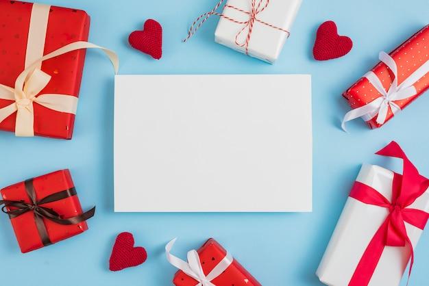Cajas de regalo de san valentín y corazones alrededor de papel.