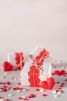 Cajas de regalo de san valentín con regalos y decoraciones. sobre fondo rosa con chispitas.