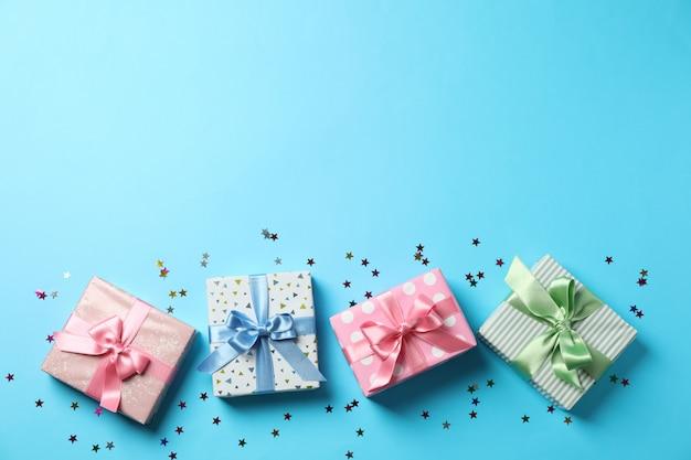 Cajas de regalo sobre fondo azul, vista superior y espacio para texto