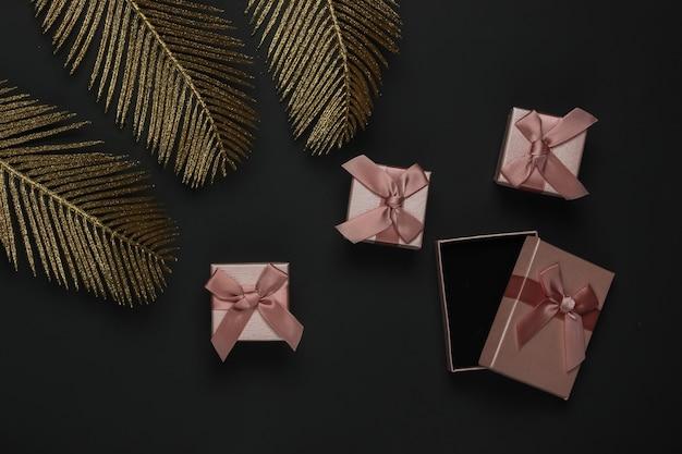 Cajas de regalo sobre un fondo negro con hojas de palmeras doradas. lay flat de moda. vista superior