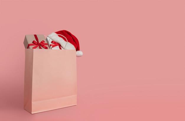 Cajas de regalo y sombrero de santa claus en bolsa de papel.