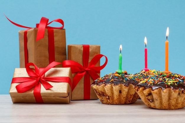 Cajas de regalo y tres sabrosos cupcakes de cumpleaños con glaseado de chocolate y caramelo, decorados con velas festivas encendidas sobre fondo azul. feliz cumpleaños concepto mínimo.