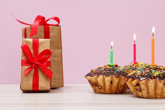 Cajas de regalo y tres sabrosos cupcakes de cumpleaños con glaseado de chocolate y caramelo, decorados con velas festivas encendidas sobre fondo lila. feliz cumpleaños concepto mínimo.