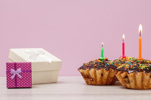 Cajas de regalo y tres sabrosos muffins de cumpleaños con glaseado de chocolate y caramelo, decorados con velas festivas encendidas sobre fondo lila. feliz cumpleaños concepto mínimo.