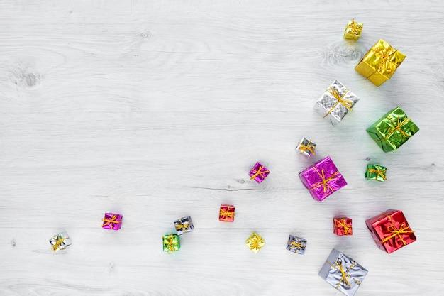 Cajas de regalo de vacaciones brillantes multicolores de varios tamaños sobre un fondo blanco.