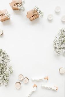 Cajas de regalo; velas; tubos de ensayo de malvavisco y flores de aliento de bebé sobre fondo blanco