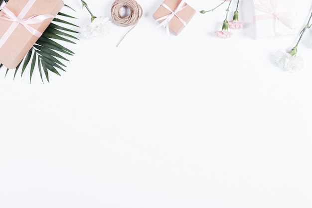 Cajas con regalos, cintas, cuerdas y flores en la mesa blanca, vista superior