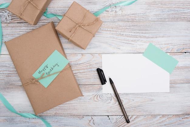Cajas con regalos de cumpleaños y papel sobre mesa de madera.