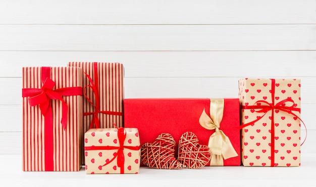 Cajas de regalos envueltas y dos corazones rojos en el fondo blanco.