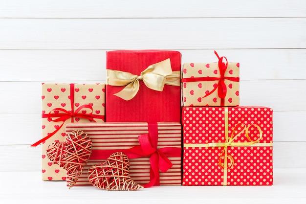 Cajas de regalos envueltas y dos corazones rojos en el fondo de madera blanco. copia espacio