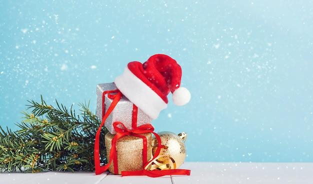 Cajas con regalos de navidad con gorro de papá noel en la parte superior.