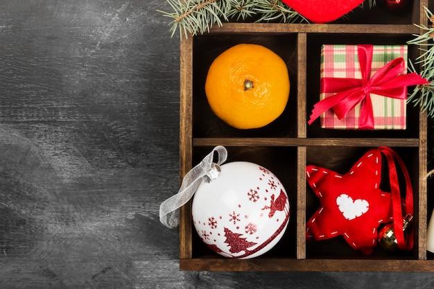Cajas con regalos para navidad y varios atributos de vacaciones en la oscuridad, vista superior, espacio de copia