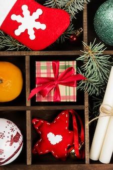 Cajas con regalos para navidad y varios atributos de vacaciones en la oscuridad, vista superior