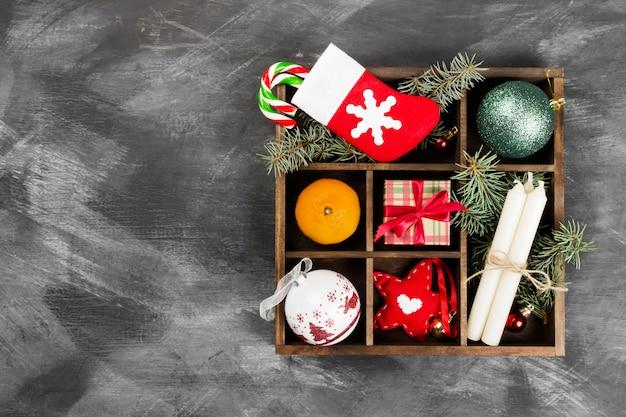 Cajas con regalos para navidad y varios atributos de vacaciones en una superficie oscura