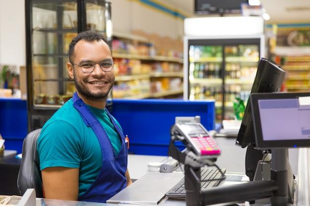 Cajero afroamericano sonriente sentado en la caja