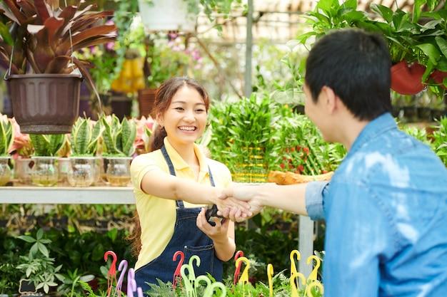Cajero bastante joven feliz en el centro de jardinería estrechar la mano del cliente y aceptar el pago