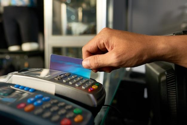 Cajero deslizando tarjeta de crédito