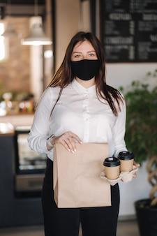 Cajero en mascarilla con paquete con comida y dos tazas de café concepto de pagos sin contacto