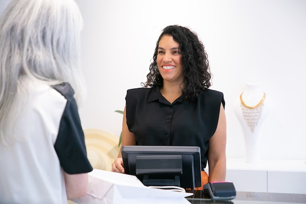 Cajero de tienda positivo feliz hablando con el cliente y riéndose de la caja. tiro medio. concepto de compras
