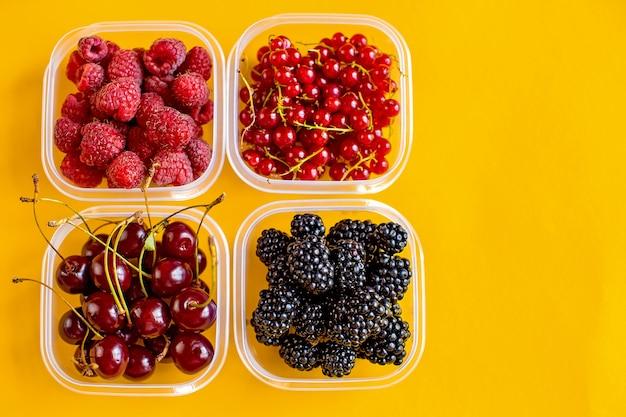 Cajitas de plástico con frambuesas, moras, grosellas rojas y cerezas.