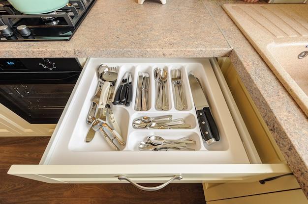 Cajón abierto de cocina con cubiertos en su interior.