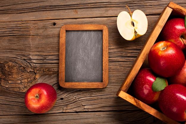 Cajón plano con manzanas maduras con pizarra.