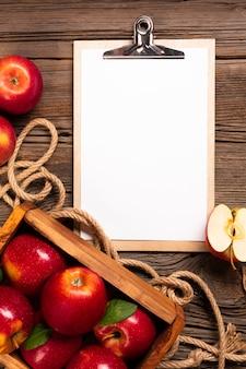 Cajón plano con manzanas maduras con portapapeles.