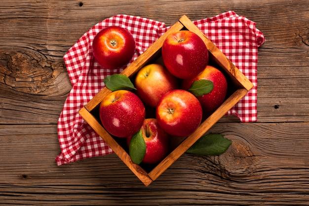 Cajón plano con manzanas maduras sobre tela.
