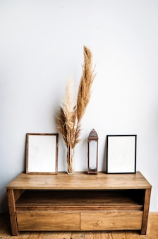 Cajonera de madera baja y elegante con decoración y marcos con un fondo blanco para texto o foto