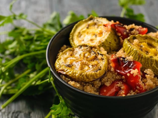 Calabacín al horno y pimiento en un recipiente negro sobre una mesa de madera. horquilla de hierro en un bol con una ensalada de verduras al horno. vista desde arriba.