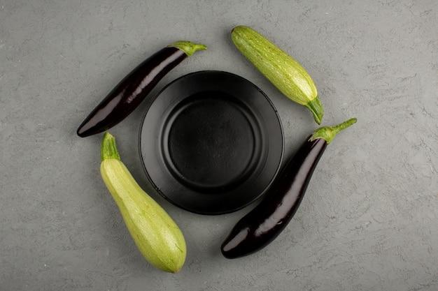 Calabacín berenjenas frescas maduras alrededor de la placa negra en un brillante