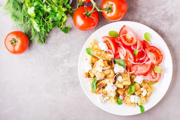Calabacín frito con queso feta, tomates, hierbas y cebollas en un plato