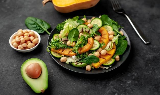 Calabaza, aguacate, pepino, garbanzos, ensalada en un plato. ensalada sabrosa y saludable