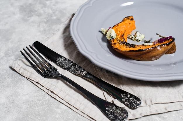 Calabaza al horno con gorgonzola sobre placa gris.