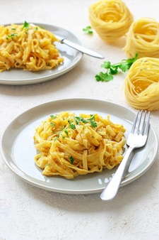 Calabaza alfredo fettucine pasta en un plato de cerámica con rodajas de calabaza cruda fresca. comida de otoño para el almuerzo. receta de calabaza moscada.