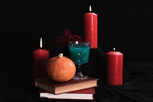 Calabaza con bebida verde y velas.