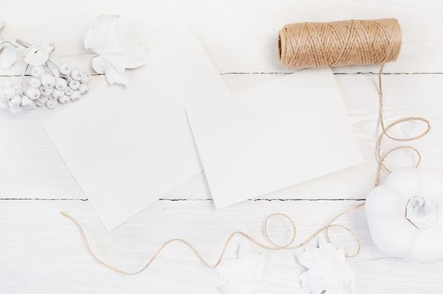 Calabaza blanca, bayas y hojas y dos hojas blancas de papel.
