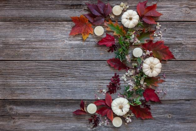 Calabaza blanca, velas, hojas de otoño y fondo de galletas en forma de murciélago